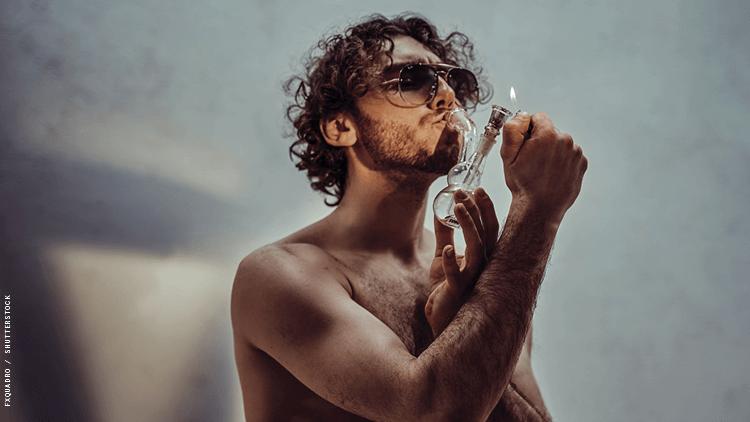 一个光着膀子的男人通过烟枪抽大麻