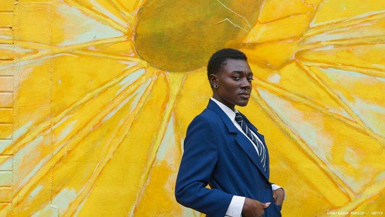 非二进制黑人穿着西装在明亮的向日葵壁画前