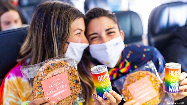 骄傲飞机上的女同性恋夫妇炫耀他们的饼干和酒