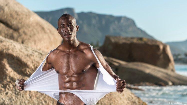 黑人男子在沙滩上撕下衬衫