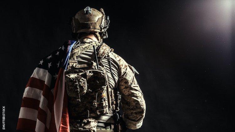 肩上扛着美国国旗的军队中的男人